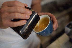 یک قهوه چی شیری را بدرون اسپرسو می ریزد
