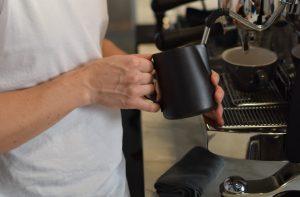 یک قهوه چی شیر را در fix cafe اسپانیا بخارپز می کند