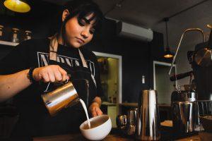 یک قهوه چی شیر را اضافه می کند