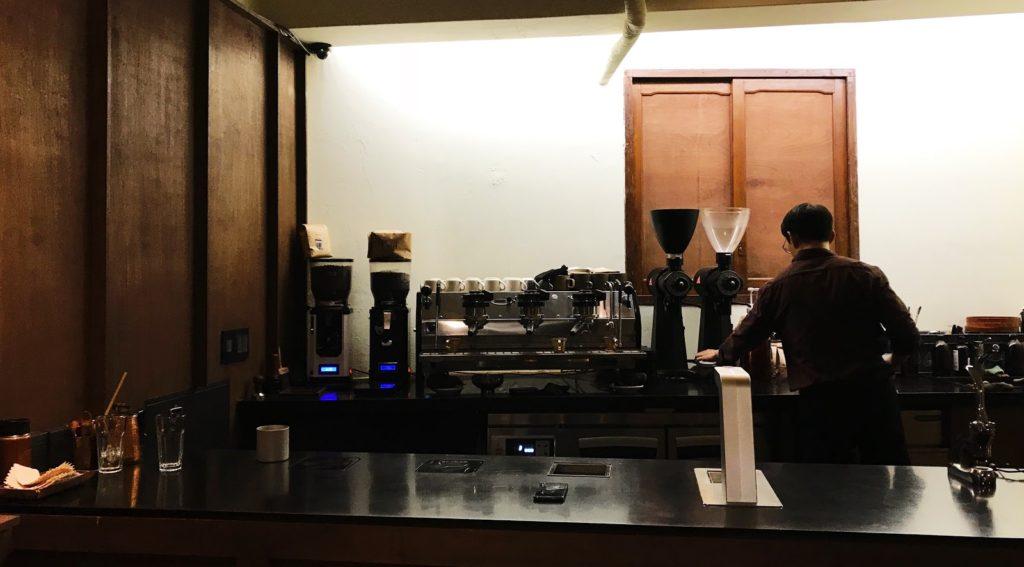 یک قهوه چی پشت پیشخوان لو کی قهوه دم می کند