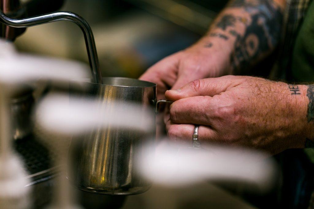 یک قهوه چی، شیر را بخار پز می کند