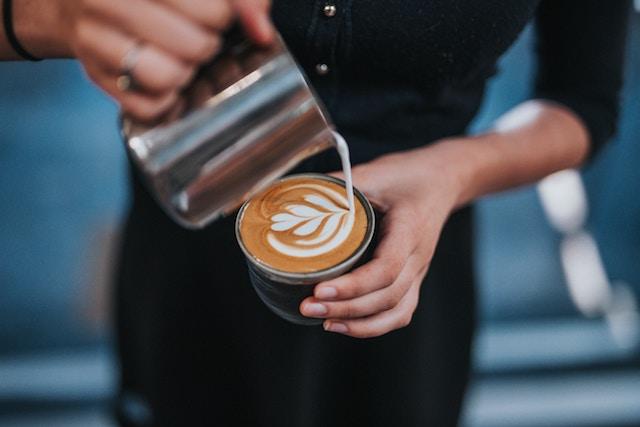 یک قهوه چی طرح لاته را می ریزد