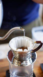 یک قهوه چی برای بلوم (شکفتن قهوه ) بر روی قهوه آب می ریزد