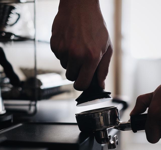 یک قهوه چی قهوه را درون پُرتافیلتر می کوبد