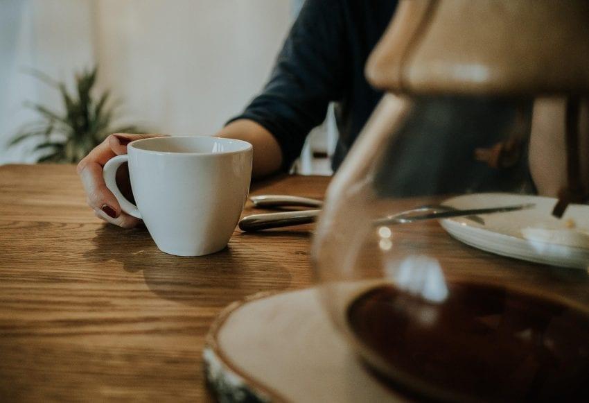 مشتری از یک فنجان قهوه لذت می برد
