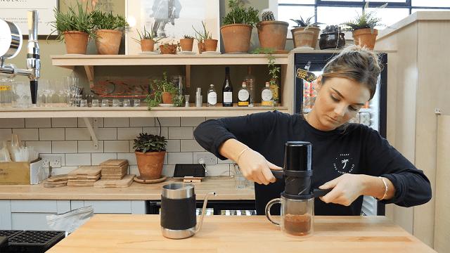 یک قهوه چی تویست پرس را می پیچاند تا قهوه را بدرون فیلتر کاغذی هدایت کند