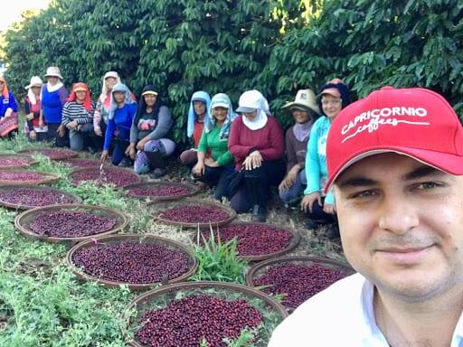 کارگران همراه گیلاس های تازه قهوه که چیده اند در Fazenda Capricornio برزیل